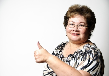 a 60 year old Hispanic woman showing the thumbs up hand sign