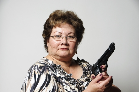 a 60 year old Hispanic woman showing she means business with her gun