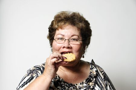snacking: a Hispanic woman snacking on a cookie between meals   Stock Photo