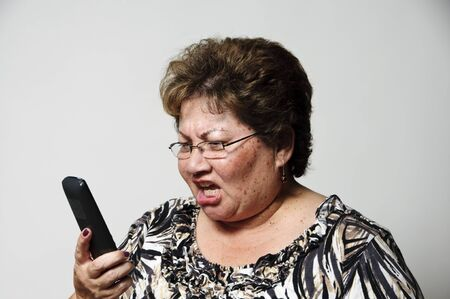 a woman yelling at the phone as she gets bad news   photo