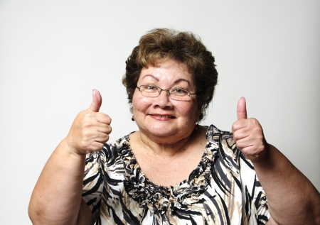 a happy older woman showing the thumbs up hand gesture