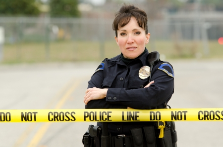 A female police officer standing in behind yellow crime scene tape. photo