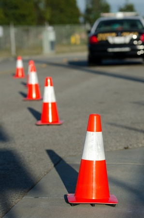 lightbar: Traffic cones set up to direct traffic around a police car. Stock Photo