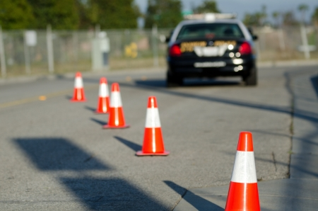 road block: Traffic cones set up to direct traffic around a police car. Stock Photo