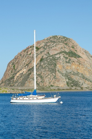 Morro Rock in the background with a sailboat sitting in Morro Bay in Central California. Stock Photo - 18860263