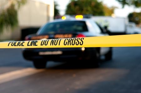 Crime scene tape in primo piano con una macchina della polizia offuscata in background in una scena del crimine.