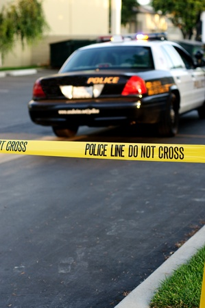 Crime scene tape in the foreground with a blurred police car in the background at a crime scene.