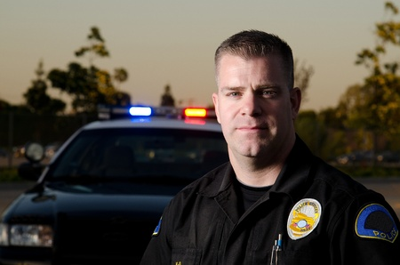 A serious looking police officer standing in front of his patrol car   Stock Photo