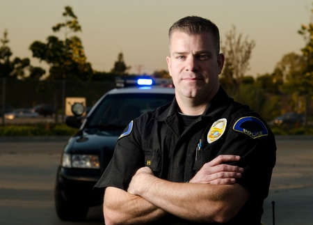 first responder: A serious looking police officer standing in front of his patrol car  Stock Photo