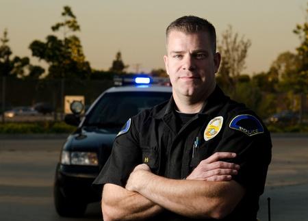 policier: Une recherche s�rieuse policier debout en face de sa voiture de patrouille Banque d'images