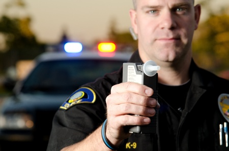 dui: A police officer holds the breath test machine for a suspect to blow into with a police car in the background  Stock Photo