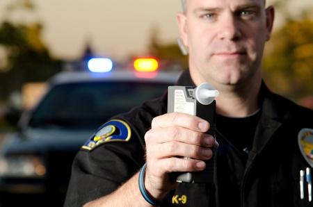Un oficial de policía tiene la máquina de prueba de aliento a un sospechoso que soplar en un coche de policía en el fondo Foto de archivo