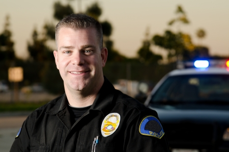25 30 years old: A smiling police officer with his patrol car in the background   Stock Photo