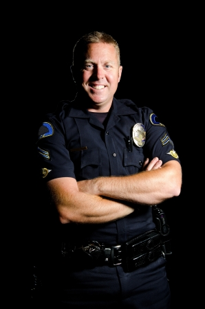 A smilng police officer with his arms crossed during his shift.  photo