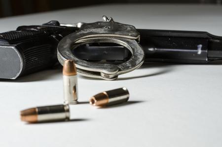 A close up di una pistola con proiettili 9 millimetri e manette. Archivio Fotografico - 22214652