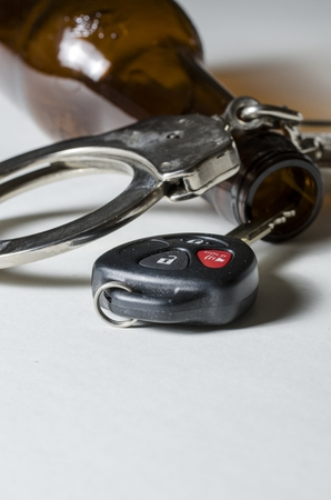 under arrest: A close up of a beer bottle with car key and handcuffs  Stock Photo