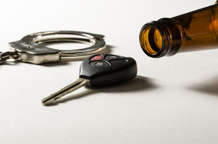 A beer bottle on its side with handcuff and car key