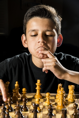 10 11 years: a boy thinking what he wants to do during a chess game