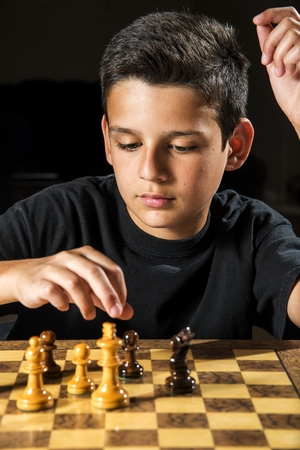 11 year old: an 11 year old boy making a move during a chess game   Stock Photo