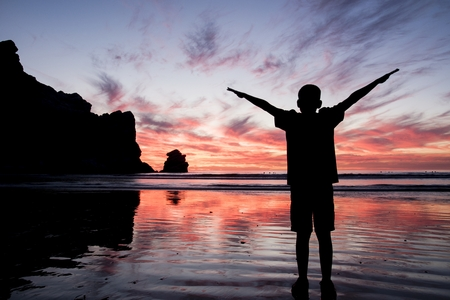 A boy holding his arms up during the sunset in Morro Bay,CA Stock Photo - 23047177