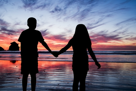 A brother and sister holding hands at sunset in Morro Bay, CA Stock Photo - 23047180