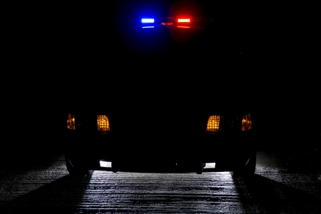 lightbar: A police car at night with its lights on   low key forcopy space left Stock Photo