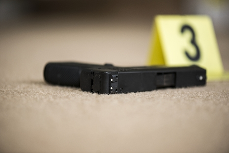 police tape: a close up of a gun at a crime scene Stock Photo