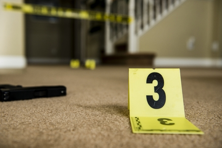 cordon tape: A hand on top of a gun at a crime scene with a marker in the foreground