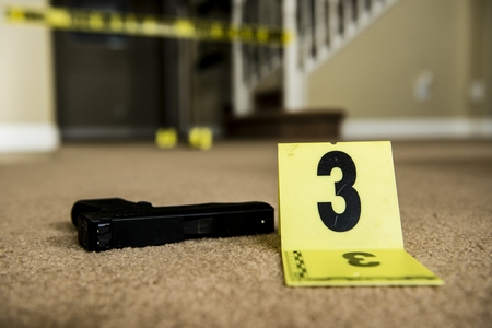 A crime scene with a gun on the ground next to an evidence marker   photo