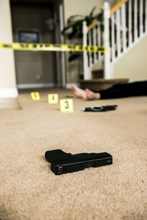 a body on the ground of a crime scene with a gun in the foreground  版權商用圖片