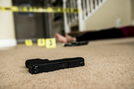 police tape: a body on the ground of a crime scene with a gun in the foreground  Stock Photo