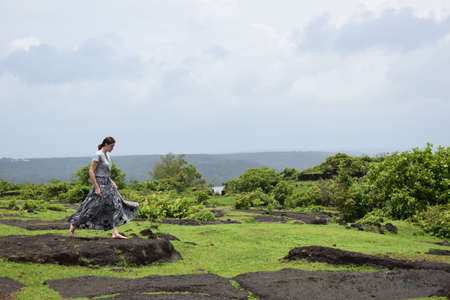 Barefoot girl in a long skirt jumping on large stones