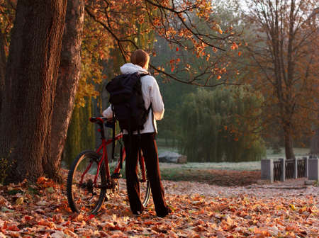Woman cyclist with bike and backpack in autumn park, lit morning sun Stock Photo