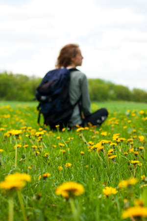 Woman traveler with a backpack sitting among green field with yellow dandelions. Tourist is out of focus photo