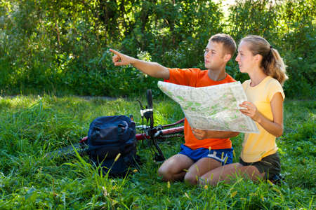 Young couple tourist read the map and show the direction against a background of green nature