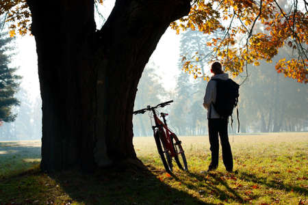 Woman cyclist lit the rays of bright morning sunlight standing near a trunk large tree photo