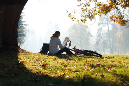 Woman cyclist with read the map sitting on halt  illuminated by the rays of bright sunlight among the green nature