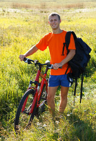 Happy man cyclist with a bicycle and a backpack on his shoulder against a background of green nature Reklamní fotografie