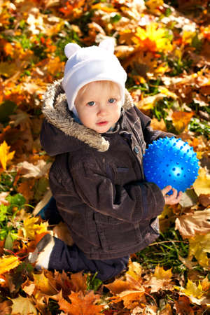 Cute child played with a blue ball in his hands. Golden autumn leaves background Stock Photo - 11963192