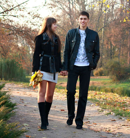 Young happy couple in love walking in park holding hands against the background of autumn nature photo