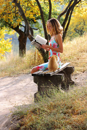 Young beautiful woman reading a book. Near it is the cat against a background of green sunlit nature photo
