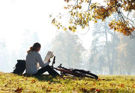 ciclismo: Mujer ciclista con leer el mapa que se sienta en alto iluminado por los rayos de la luz del sol entre el verde de la naturaleza