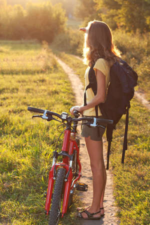 Woman cyclist with a backpack behind shoulders carefully scrutinizes the direction