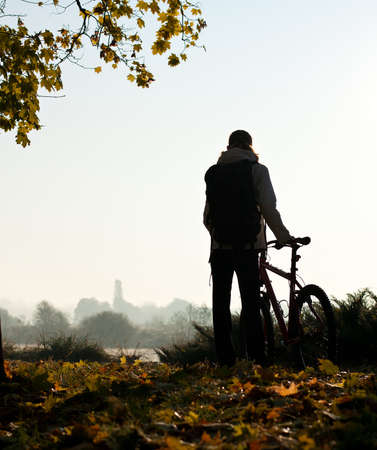 Silhouette of woman with bicycle with beautiful nature by the break of day Фото со стока
