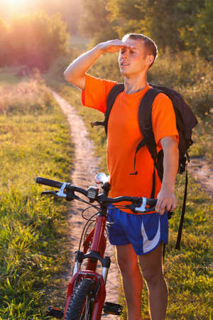 Man cyclist with a backpack behind shoulders carefully scrutinizes the direction against the background evening summer nature photo