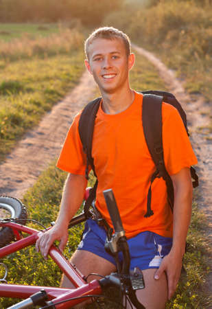 Happy man cyclist sitting against a background of solar evening summer green nature photo