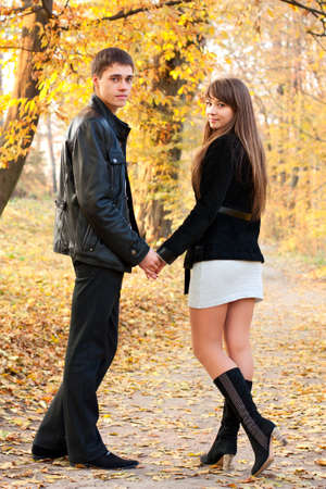 Young beautiful couple in love holding hands against the background of autumn park in defoliation