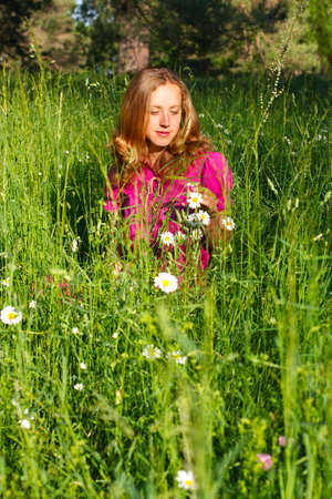 Beautiful young woman sitting in grasses and chamomile. Summertime outdoors photo