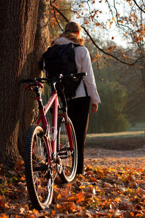 Woman cyclist with bike and backpack in autumn nature on the morning, lit morning sun