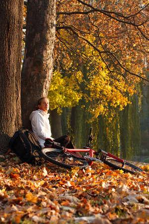 relaxes: Relaja ciclista de la mujer con la bicicleta se encuentra entre las hojas ca�das en oto�o de parque iluminado por los rayos del sol y disfrutar de la recreaci�n